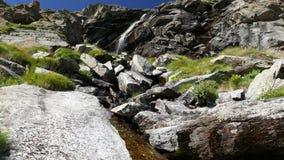 Cascadas que fluyen en el ambiente incontaminado idílico que cruza prados y los cantos rodados verdes en las montañas en verano almacen de metraje de vídeo