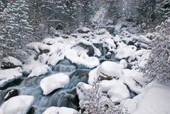 Cascadas y nevadas de la cala de la montaña del invierno Imagenes de archivo