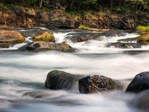 Cascadas y registros y rocas cubiertos de musgo fotos de archivo