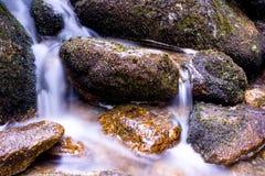 Cascade à écriture ligne par ligne au-dessus des roches image libre de droits