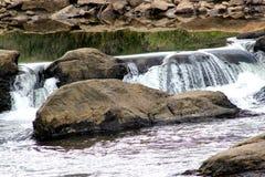 Cascade à écriture ligne par ligne au-dessus de grandes roches Image stock