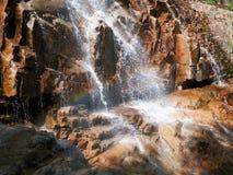 Cascade à écriture ligne par ligne au-dessus des roches Images stock
