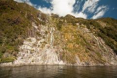 Cascade à écriture ligne par ligne chez Milford Sound Photo libre de droits