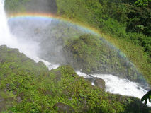 Cascade à écriture ligne par ligne dans la forêt humide équatoriale, avec l'arc-en-ciel arqué Images stock