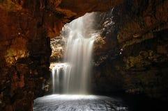 Cascade à écriture ligne par ligne dans une caverne Photos libres de droits