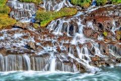 Cascade à écriture ligne par ligne de Hraunfossar dans HDR, Islande Image stock