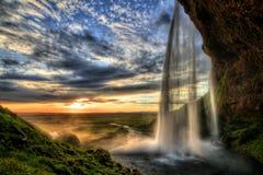 Cascade à écriture ligne par ligne de Seljalandfoss au coucher du soleil dans HDR, Islande Photos stock
