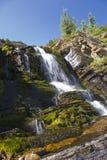 Cascade à écriture ligne par ligne de stationnement national de lacs Waterton Photographie stock libre de droits