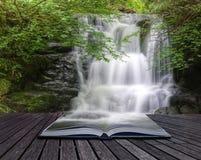 Cascade à écriture ligne par ligne entrant au-dessus des roches dans les pages du livre photos libres de droits
