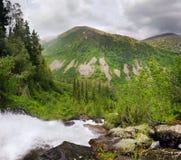 Cascade à écriture ligne par ligne et montagnes Photographie stock libre de droits