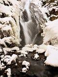Cascade à écriture ligne par ligne figée Crique d'hiver, pierres glaciales et branches Image stock