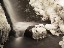 Cascade à écriture ligne par ligne figée Crique d'hiver, pierres glaciales et branches Images stock