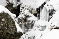 Cascade à écriture ligne par ligne figée parmi des roches Photos libres de droits