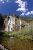 Cascade à écriture ligne par ligne montant en cascade au-dessus de la roche Images stock
