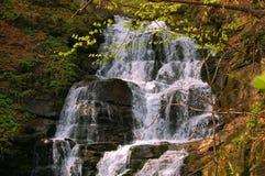 Cascade à écriture ligne par ligne parmi les roches Image libre de droits