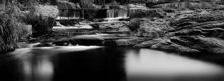 Cascade à écriture ligne par ligne rapide de fleuve panoramique en noir et blanc photos stock