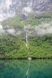 Cascade à écriture ligne par ligne reflétée dans le lac Lovatnet, Norvège Photo libre de droits