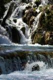 Cascade à écriture ligne par ligne rocheuse sur le fleuve Images stock