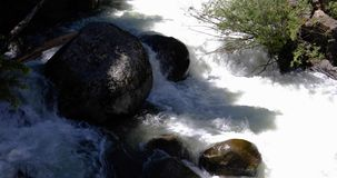 Cascade around large rocks 4k 24fps. Cascade around large rocks in river stock video footage
