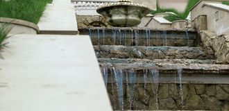 Cascade artificial waterfall of old stone. And decorative vase stock image