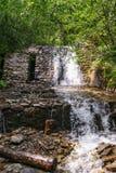 Cascade blanche et mur de maçonnerie en pierre de jardin de rocaille Images stock
