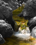 Cascade in colourless stones. Greenish water flows on the decoloured stones forming a falls stock photos