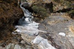 Cascade congelée parmi les roches Image libre de droits