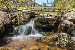 Cascade creek and wooden footbridge Royalty Free Stock Photos