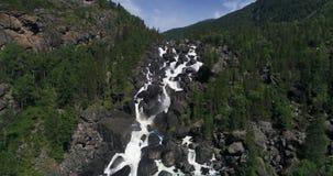 Cascade d'Ucharsky avec un arc-en-ciel pendant l'été parmi les montagnes banque de vidéos