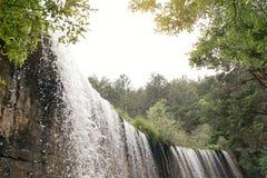 Cascade dans le lac de montagne et le parc vert dans Rascafria Photographie stock libre de droits