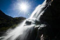 Cascade dans les montagnes, dans le côté, dans le contre-jour, le soleil dans le cadre, éclat du soleil Dombay, cascade d'Alibek images stock