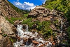 Cascade dans les roches contre le contexte des montagnes et du ciel avec des nuages Photographie stock libre de droits