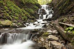Cascade de rochers sur la cascade d'une rivière rapide de montagne entre les collines des montagnes carpathiennes Photos libres de droits