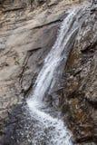 Cascade en bas de la falaise pure de roche frappant l'obstruction et pulvérisant en longueur entouré par la roche humide images stock