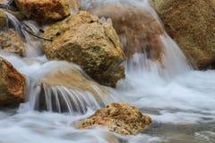 Cascade et roches couvertes de la mousse Photographie stock libre de droits