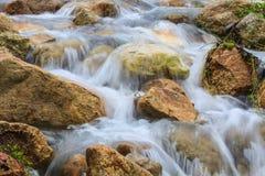 Cascade et roches couvertes de la mousse Photos libres de droits