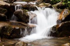 Cascade falls over mountain rocks Royalty Free Stock Photography
