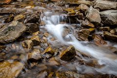 Cascade falls over mountain rocks Royalty Free Stock Images