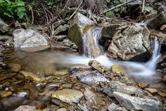 Cascade falls over mountain rocks Stock Image