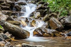 Cascade falls over mountain rocks Royalty Free Stock Photo