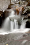 Cascade falls over old plum river with rocks Stock Images