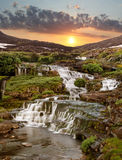 The cascade of falls on a sunset in mountains Royalty Free Stock Image