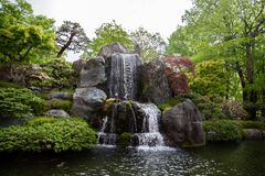 Cascade flowing over mossy boulders in a garden. royalty free stock images
