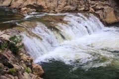 Cascade of Foamy Waterfalls along Brown Stones Royalty Free Stock Photos