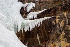 Cascade glaciale à la falaise de roche dans l'horaire d'hiver Image libre de droits