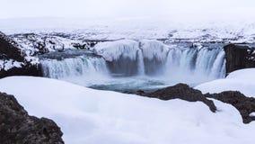 Cascade glaciale épique au milieu d'un paysage neigeux rocheux Photos libres de droits