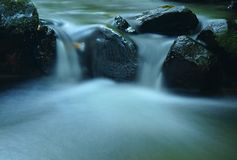 Cascade on mountain stream, water is running over basalt boulders and bubbles create on level milky water. Stock Photo