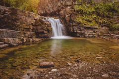 Cascade mountain waterfall with small lake in front Royalty Free Stock Images