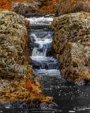 Cascade par les roches faites un pas naturelles Photos stock