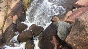 Cascade parmi les grandes pierres banque de vidéos